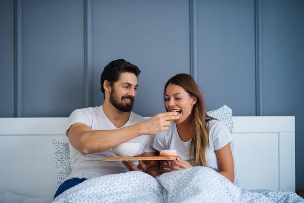 Привлекательный молодой счастливый довольный мужчина кормит свою великолепную девушку в постели дома или в отеле.