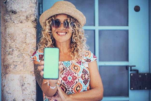 サングラスと麦わら帽子の魅力的な若いヒップスターの女性が壁にもたれて携帯電話の画面を表示しています。携帯電話の画面でエキサイティングなオファーや割引を示すスタイリッシュな女性