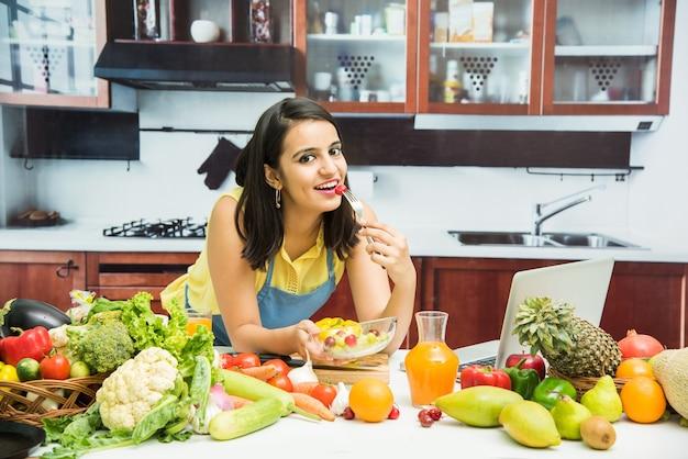 Привлекательная молодая индийская девушка с фартуком готовит на кухне со столом, полным фруктов и овощей