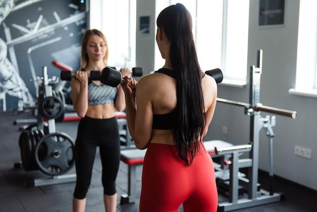 ダンベルで運動するスポーツウェアの形の良い体を持つ魅力的な若い女性