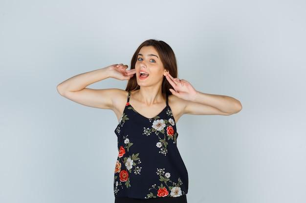 Attraente giovane donna in camicetta tenendo le dita vicino alle orecchie e guardando meravigliata, vista frontale.