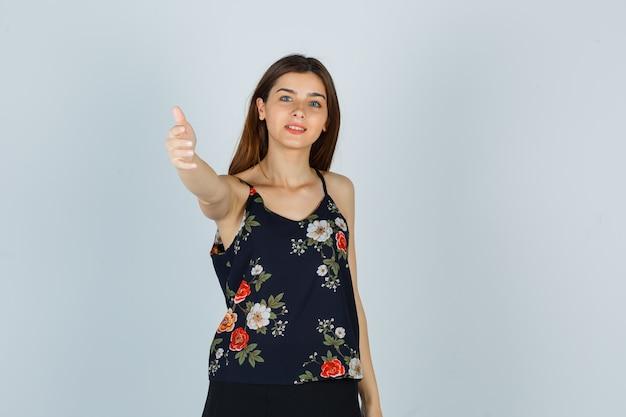 Attraente giovane donna in camicetta che invita a venire a guardare dolce, vista frontale.