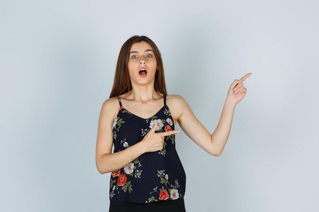 Attraente giovane donna in camicetta che punta all'angolo in alto a destra e sembra meravigliata, vista frontale.