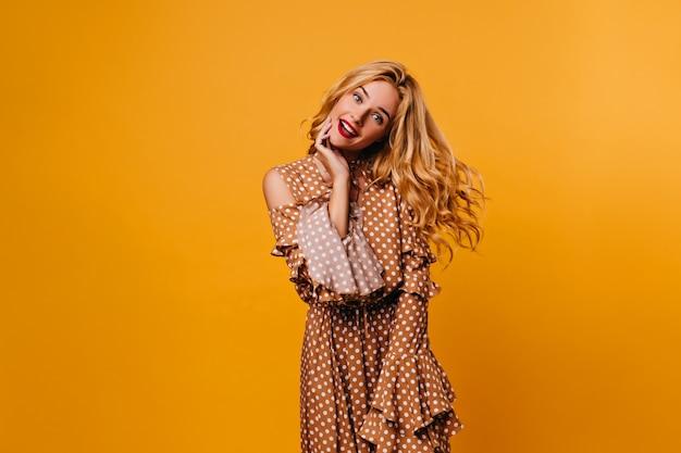 Attraente giovane signora divertendosi sulla parete gialla. ragazza riccia ispirata nella retro posa del vestito