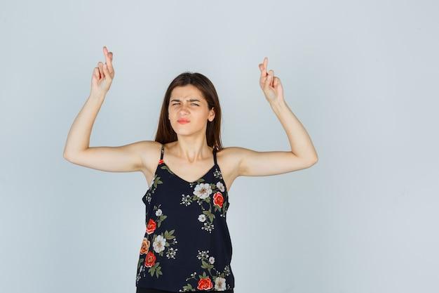 Attraente giovane donna che tiene le dita incrociate mentre si acciglia in camicetta e sembra sicura, vista frontale.
