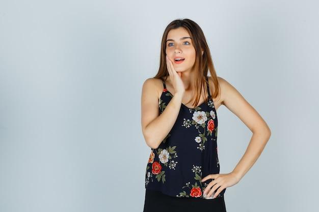 Attraente giovane donna che tiene la mano sulla guancia in camicetta e sembra meravigliata, vista frontale.