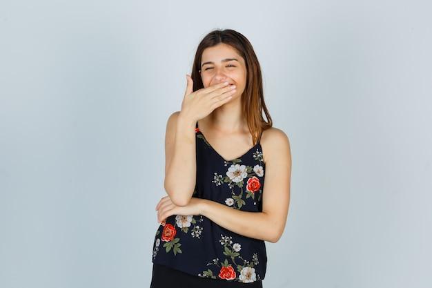Привлекательная молодая леди, взявшись за рот, улыбаясь в блузке и выглядела веселой, вид спереди.