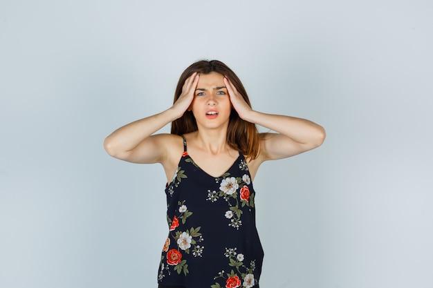 Attraente giovane donna che si tiene per mano sulla testa in camicetta e sembra infastidita. vista frontale.