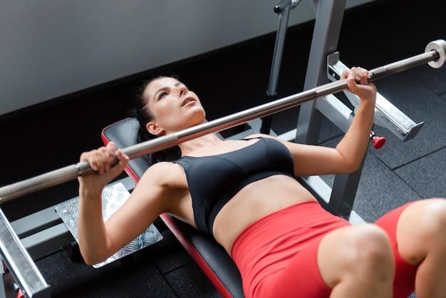 ベンチとトレーニングの腕の上に横たわっている黒いブラと赤いショートパンツの魅力的な若い女性