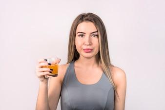 飲み物のガラスとスポーツウエアで魅力的な若い女性