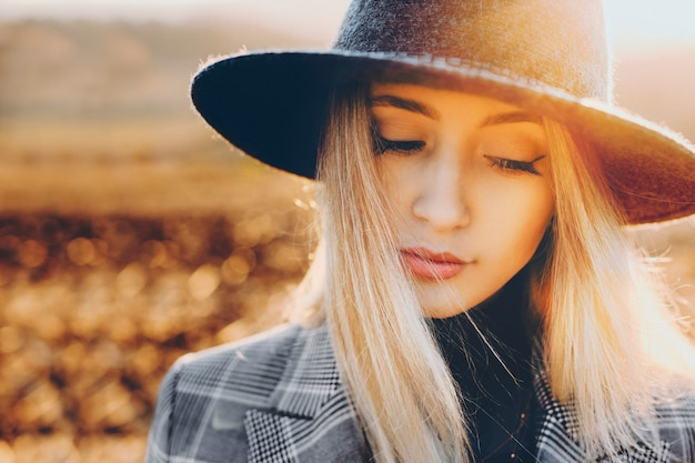 素晴らしい晴れた日に自然のぼやけた背景の上に立っている間見下ろしているスタイリッシュな帽子の魅力的な若い女性。田舎で見下ろしているかわいい女性