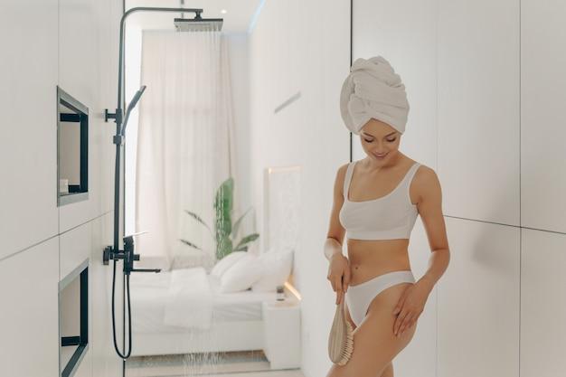 Привлекательная молодая леди в белом нижнем белье делает скрабирующий массаж сухой щеткой перед утренним душем в светлой ванной комнате на фоне стильной спальни. концепция красоты и гигиены женщин