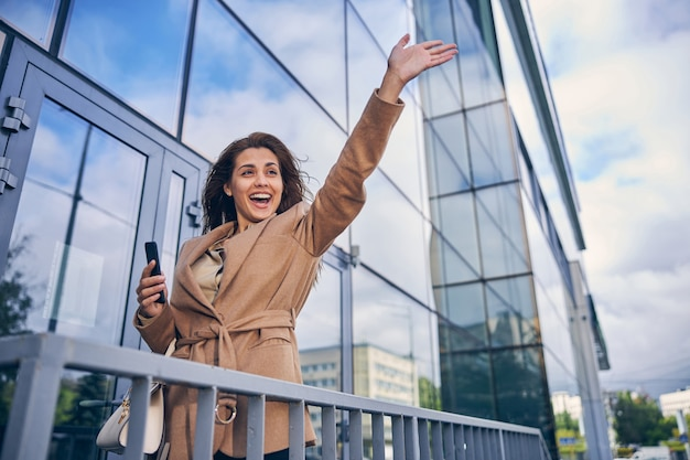 Attractive young lady looking excited while holding mobile phone in her hand and waving somebody