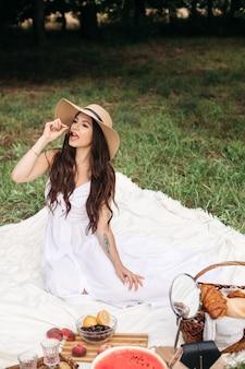 공원에서 나무 근처 포즈를 취하는 매력적인 젊은 아가씨