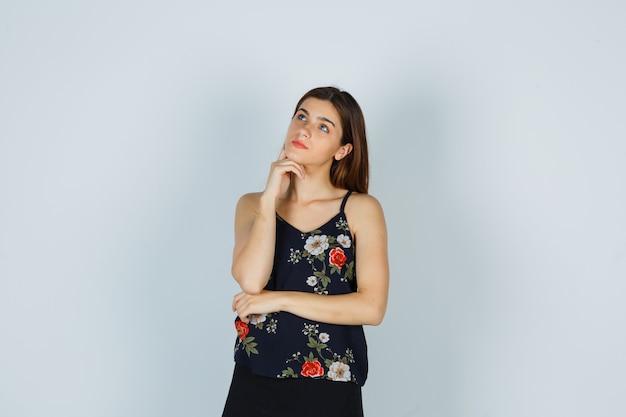 魅力的な若い女性がブラウスで手に顎を支え、物思いにふける、正面図。