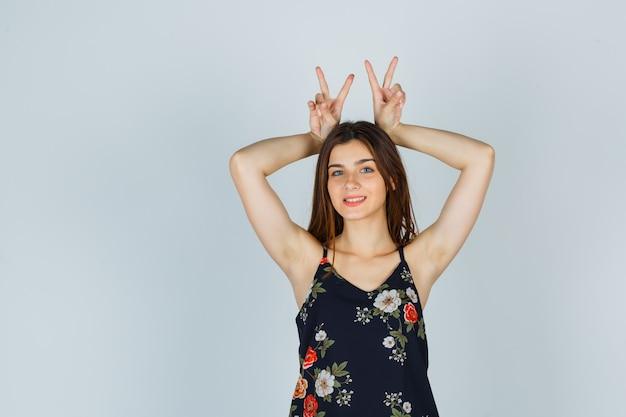 Attraente giovane donna che mostra il gesto delle orecchie da coniglio in camicetta e sembra divertente. vista frontale.