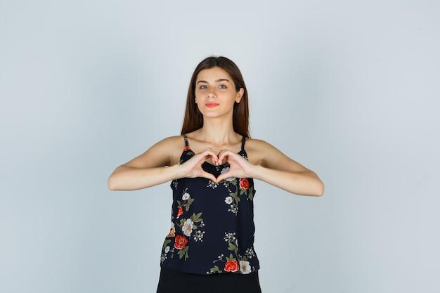 Attraente giovane donna che mostra il gesto del cuore in camicetta e sembra sicura. vista frontale.