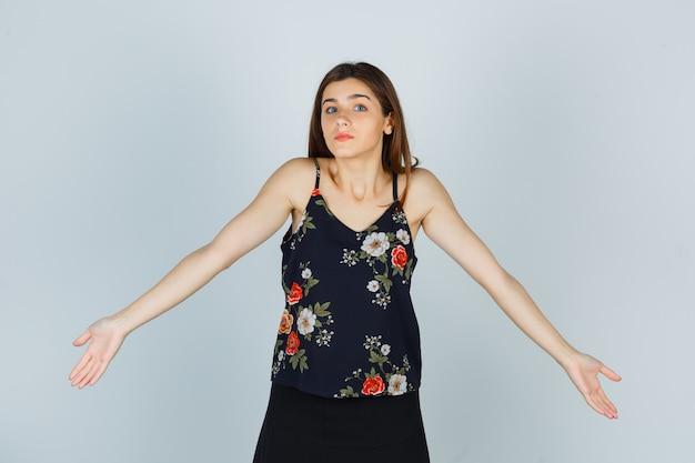 Привлекательная молодая леди показывает беспомощный жест, протягивая руки в блузке и выглядит смущенным. передний план.
