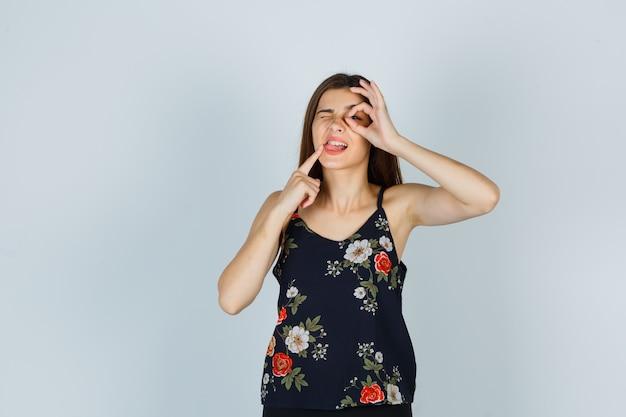 매력적인 젊은 여성이 눈에 확인 표시를 하고, 입 근처에 손가락을 잡고, 블라우스를 입고 생각에 잠긴 채 혀를 내밀고 있습니다. 전면보기.