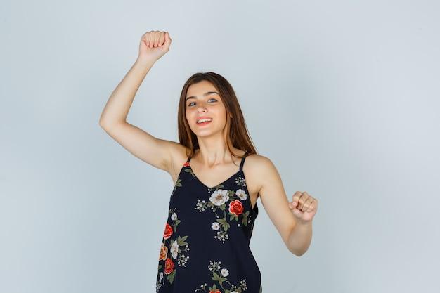 ブラウスで勝者のジェスチャーを示し、幸せそうに見える魅力的な若い女性。正面図。