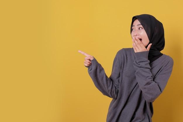 매력적인 젊은 아가씨 놀라움과 그녀의 손을 사용하여 식을 가리키는