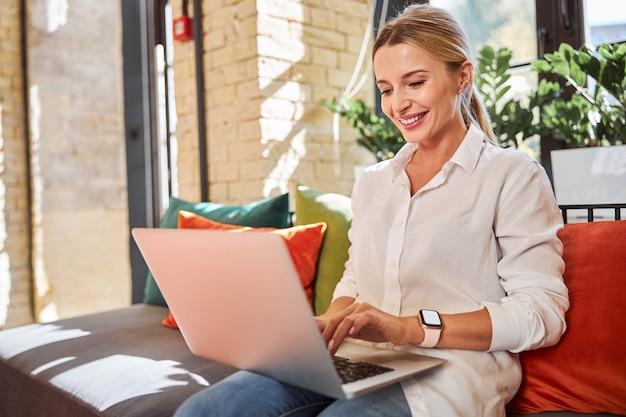 Привлекательная молодая леди, используя современный ноутбук в кафе