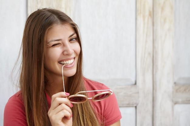 Привлекательная молодая дама с красивыми волосами флиртует, подмигивает, держит в руках солнцезащитные очки и с игривой улыбкой кусает кончик виска.