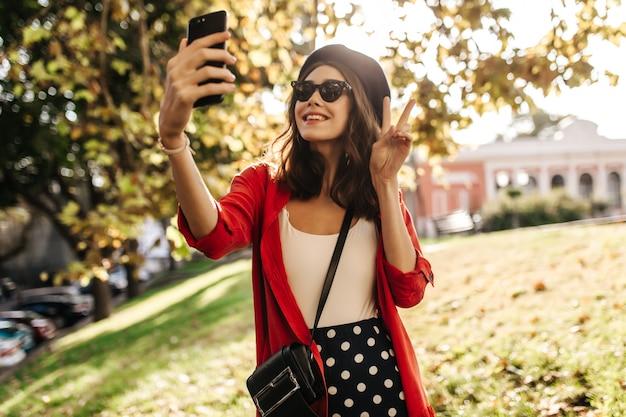 갈색 머리, 베레모, 짙은 선글라스가 야외에 서 있고 손에 전화로 화상 채팅을 하는 매력적인 젊은 여성