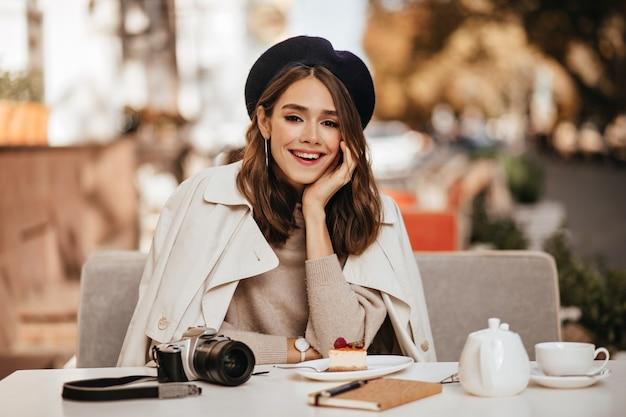 갈색 물결 모양의 헤어스타일, 베레모, 베이지색 트렌치 코트를 입은 매력적인 젊은 여성이 화창한 가을 도시 벽을 배경으로 카페 테라스에서 점심을 먹고 있습니다.