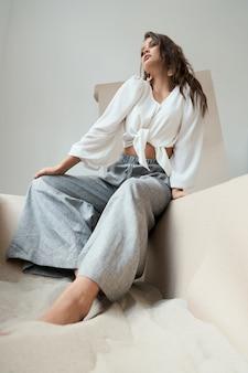 Привлекательная молодая леди с волнистыми длинными волосами в белой перевязанной блузке и серых брюках сидит на краю большой бумажной коробки, полной морского песка. профессиональная модель позирует на камеру.