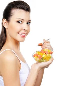 Привлекательная молодая смеющаяся девушка ест фрукты цитрусовый десерт