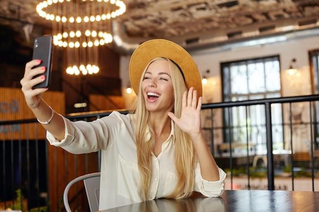 Привлекательная молодая длинноволосая блондинка сидит за столиком в кафе во время обеденного перерыва, фотографирует себя со своим смартфоном, поднимает ладонь в жесте приветствия и широко улыбается