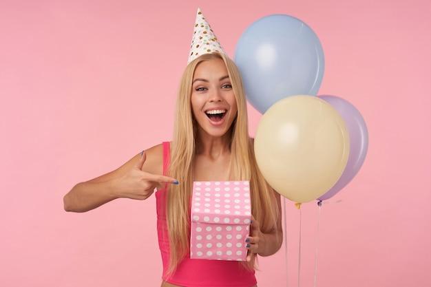 ピンクのトップとコーンの帽子で休日を祝う魅力的な若い長い髪の女性、ギフト包装された箱を持って、ピンクの背景の上に隔離され、カメラを楽しく見ながら、中身を興奮させます
