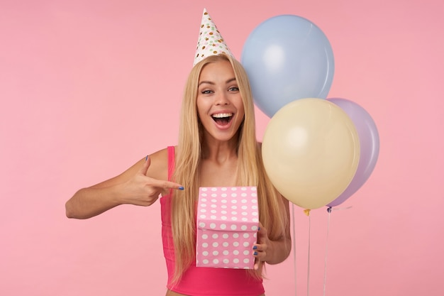 Attraente giovane donna dai capelli lunghi con top rosa e cappello a cono che celebra la festa, che tiene la scatola incartata e che eccita quello che c'è dentro, isolato su sfondo rosa, guardando la telecamera con gioia