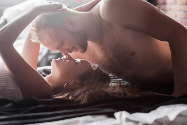 매력적인 젊은 연인들이 호텔 방에서 섹시한 란제리를 입고 침대에서 함께 연주 커플이 있습니다.