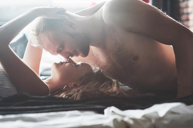 魅力的な若い恋人たちは、ホテルの部屋でセクシーなランジェリーを着て、ベッドで一緒に遊んでいるカップルを持っています。