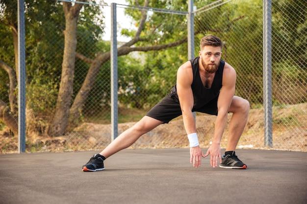 야외에서 다리를 뻗고 있는 매력적인 젊은 남성 운동선수