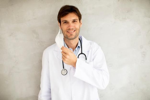 魅力的な若い男性医師が壁のそばに立っている間に彼の外科用保護マスクを脱いでいます