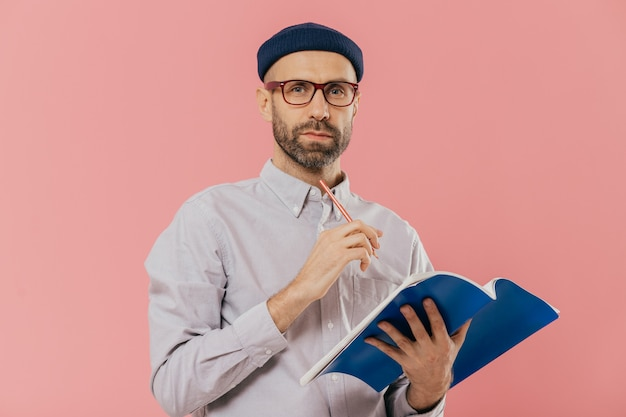 Attractive young male holds textbook, makes notes in organizer, dressed formally.