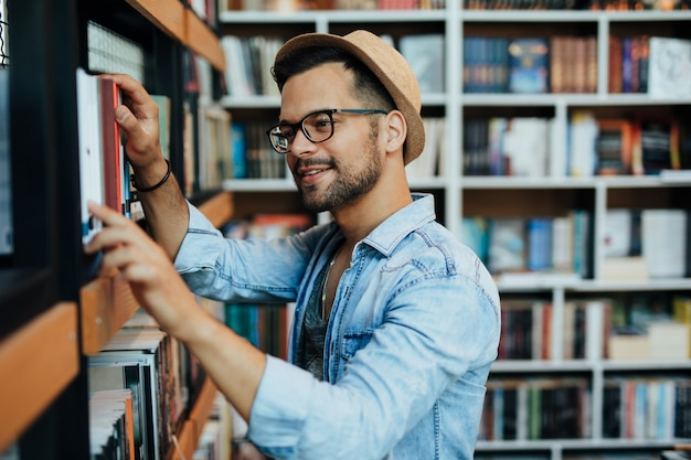Attractive young male student choosing books in the bookstore