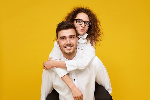 眼鏡をかけた彼の愛らしいガールフレンドにピギーライドを与える剛毛を持つ魅力的な若い男性。彼氏の背中に乗って幸せそうに笑うスタイリッシュな女性。交際と関係
