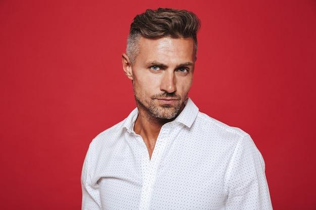 Привлекательный молодой человек 30-х годов с щетиной в белой рубашке, изолированной на красном
