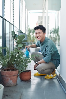 Attractive young man on apartment balcony watering plants in box from blue watering can
