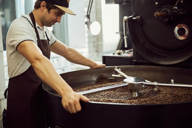Attractive young man in apron looking at cooling tray with freshly roasted coffee beans and smiling