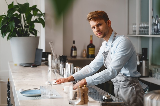 Attractive young man in apron looking and smiling while working in cafe
