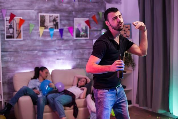 Giovane attraente che balla una bottiglia di birra in mano a una festa mentre i suoi amici stanno dormendo.