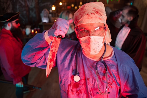 Attractive young man in a doctor costume holding a knife at halloween party. halloween night life.