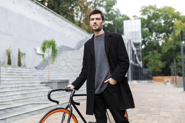 Привлекательный молодой человек, одетый в пальто, гуляет с велосипедом по улице