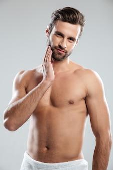分離された立っているタオルに身を包んだ魅力的な若い男