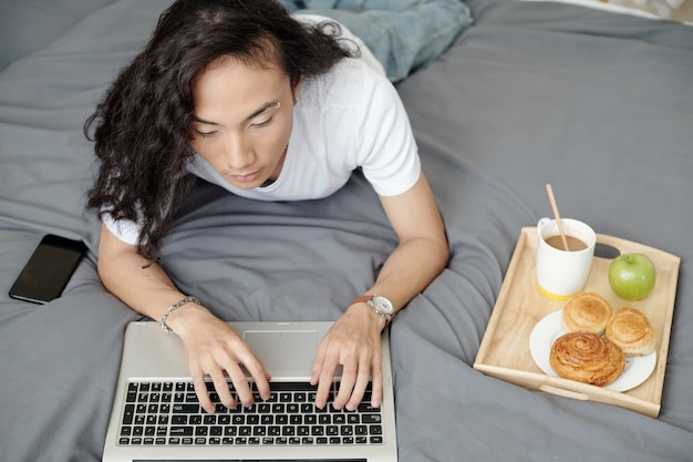 Attractive young man eating breakfast in bed and typing on laptop